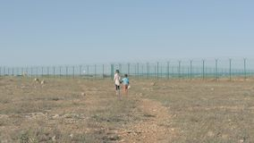Children walk a dirt path circa in the refugee camp. concept Immigration crisis poor boy and his sister need of help
