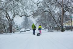 Kids pulling a sled down a quiet snow covered street. Children walk down the center of an empty street dragging sleds in the freshly fallen winter snow Royalty Free Stock Photos