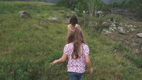 Children walk down the meadow. two little girls traveler was walking across a field near a mountain river.  stock video