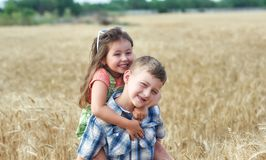 Children on a walk in a field of wheat . Funny brother and sister in the countryside stock photography