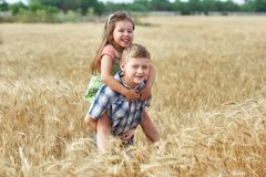 Children on a walk in a field of wheat . Funny brother and sister in the countryside royalty free stock photos