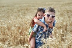 Children on a walk in a field of wheat . Funny brother and sister in the countryside royalty free stock image