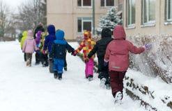 Children on walk in kindergarten in the winter. Stock Images