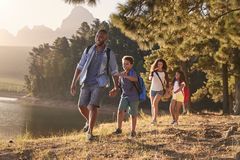 Children Walk By Lake With Parents On Family Hiking Adventure stock photography