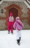 Children walk in snow to  school building Stock Photo