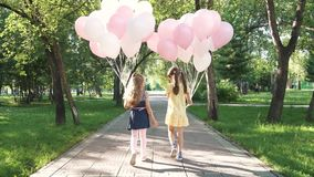 Children walk through summer Park with balloons. two little girls are holding a lot of colorful balloons. the view from. Children run through the Park with a stock footage