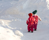 Children walking. Two small children walking on a snowy road Stock Image