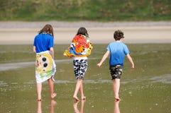 Children walking along the beach stock image