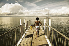 Children walking along a small jetty in Lake Leman Stock Photos