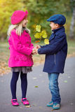 Children walking in beautiful autumn park on warm sunny fall day. Happy children walking in beautiful autumn park on warm sunny fall day Stock Photo