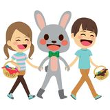 Children Walking Easter Bunny. Cute little children walking together with Easter bunny holding hands carrying colorful egg basket Stock Photo