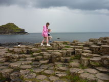 Children walking on Giant's Causeway basalt columns. A popular tourist destination in Northern Ireland stock image
