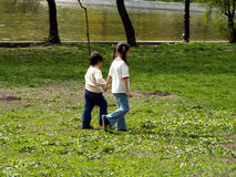 Children walking in the park. Children in the park walking hand in hand stock photo