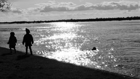 Children walking. By the river black and white photo Stock Image