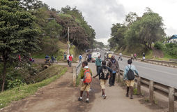Children walking in the road. Of Arusha in Tanzania surrounded by trees. Picture taken in May 2014 royalty free stock images