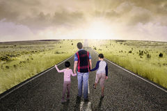 Children walking on the road with dad Stock Photo