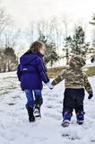 Children walking in snow holding hands Stock Image