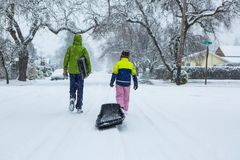 Children walking through a snowy neighborhood with a sled. Children walk down the center of an empty street dragging sleds in the freshly fallen winter snow Royalty Free Stock Photo