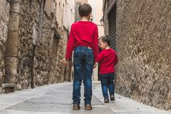 Children walking on their backs on the street. Concept of friendship between children Stock Photo