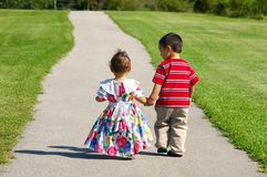 Children walking together on a sidewalk. Back view of a young boy and baby girl strolling on a concrete path with a grassy field on both sides, with blurred stock photography