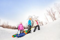 Children walking up the snowy hill and carry tubes Royalty Free Stock Photo