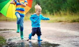 Children walking in wellies in puddle on rainy weather royalty free stock images