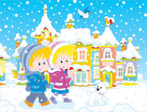 Children walking through a winter town Royalty Free Stock Photo
