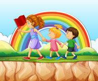 Children walking after woman on cliff Royalty Free Stock Image