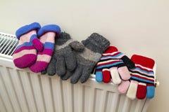 Children& x27; warme handgestrickte gestreifte woolen Handschuhe s, die auf hea trocknen Stockfotos