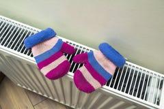 Children& x27; warme handgestrickte gestreifte woolen Handschuhe s, die auf hea trocknen Stockbilder