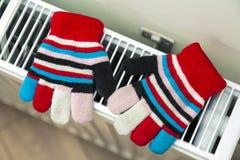 Children& x27; warme handgestrickte gestreifte woolen Handschuhe s, die auf hea trocknen Lizenzfreie Stockfotos