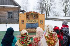 Children watch the performance of puppet theatre during the Shrovetide celebration. Stock Photo
