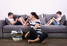 Children watch the tablets and their mother tries to read them book. Royalty Free Stock Photography