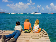Children watching the bequia easter regatta from the end of a jetty Royalty Free Stock Image
