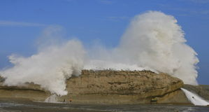 Children watching large wave crashing over rock Royalty Free Stock Images