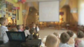 Children watching the pictures using a projector stock video footage