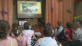Children watching the pictures using a projector stock footage