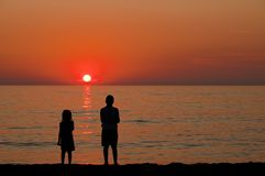 Children watching the sunset. On the beach Stock Photography