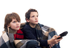 Children watching television. Covered with a blanket, isolated on a white background Stock Photography