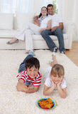 Children watching television on floor Stock Photos