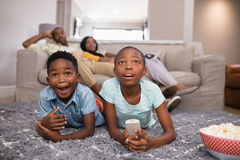 Children watching television while parents sitting at home Stock Photos
