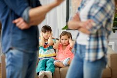 Children watching their parents quarreling at home. Family problem, conflict and people concept - sad children watching their parents quarreling at home royalty free stock image