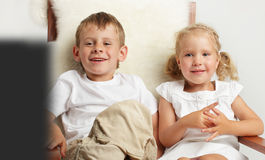 Children watching TV. Brother and sister watching TV at home Stock Photo