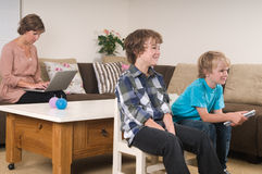 Children watching tv. Children are watching tv while mother is working in the background Royalty Free Stock Photo