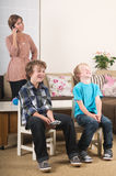 Children watching tv. Children are watching tv while mother is calling in the background Stock Photography