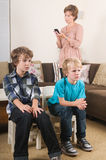 Children watching tv. Children are watching tv while mother is calling in the background Royalty Free Stock Image