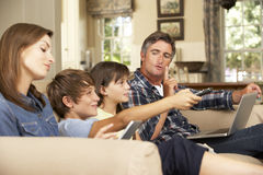 Children Watching TV Whilst Parents Use Laptop And Tablet Computer At Home Stock Image