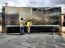 Children by water feature. Two young boys enjoying playing by a steel water feature Royalty Free Stock Photography