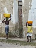 Children with watercans on Island of Mozambique. Two children carrying cans with water on their head, on Island of Mozambique. Ilha de Mocambique, in Africa Stock Photo