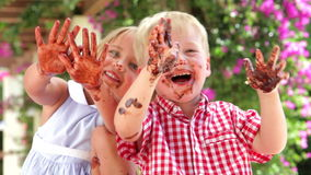 Children Waving Chocolate Covered Hands At Camera